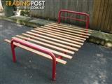 Red tubular bed base with oak slats